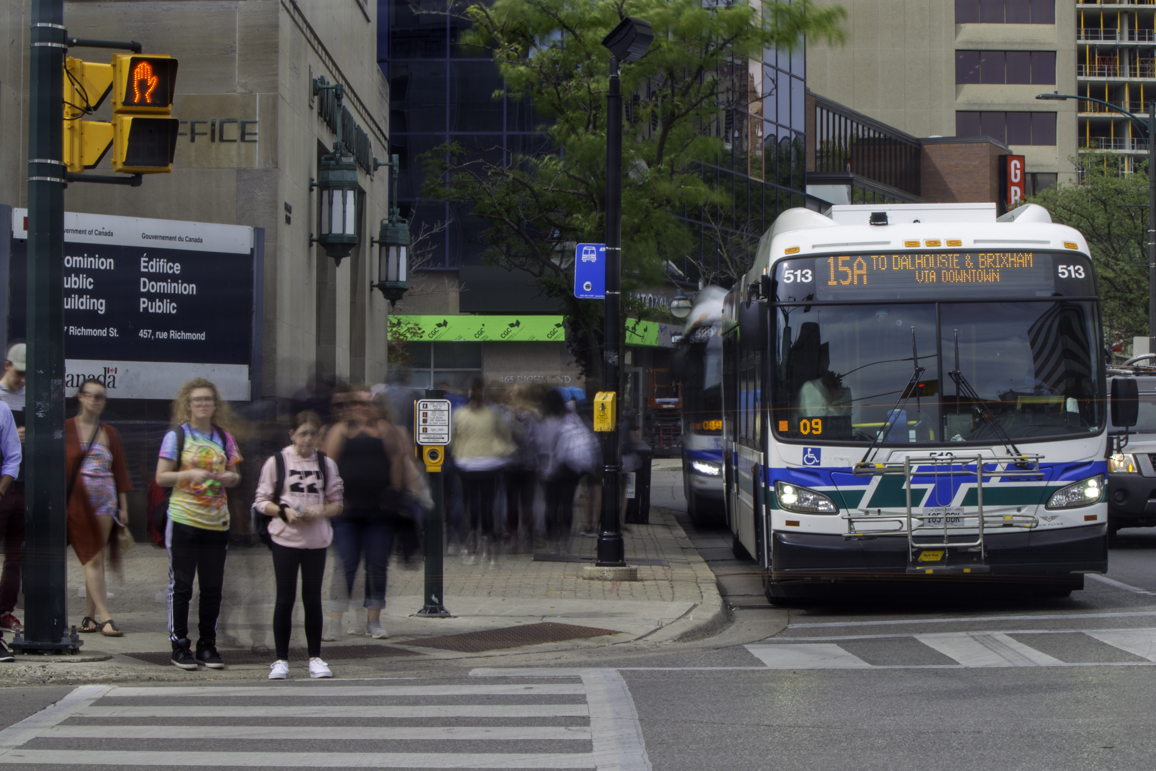 a bus and pedestrians at a downtown intersection