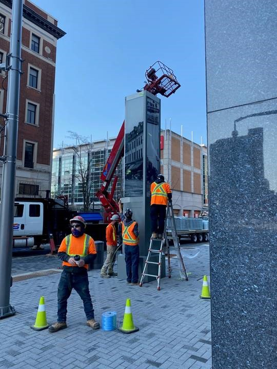 Crew members installing one of three gateway markers on Dundas Place earlier today.